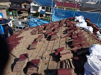 江戸川区のアパート屋根葺き替え工事の工事の様子、既存の瓦を屋根からおろしている