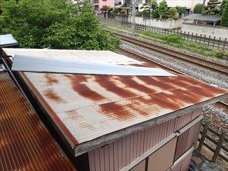 屋根が吹き飛ばされた波板屋根の物置