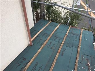 瓦棒の間にガルバリウム鋼板の屋根を嵌め込んでいきます