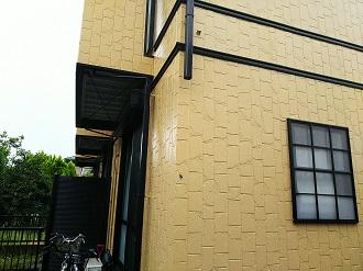 雨樋の外れた黄色い外壁の住まい