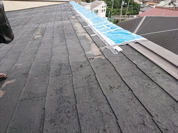 スレート葺きの片流れ屋根の先に棟板金が設置してあります