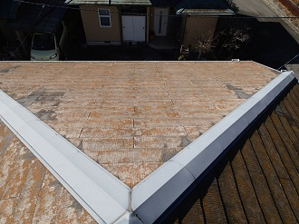 塗装の剥がれたスレート屋根と棟板金