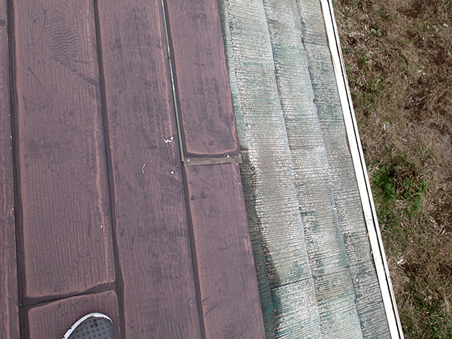 金属屋根が剥がれた箇所からスレート屋根が露出