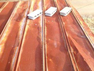 剥がれて補修跡のある金属屋根